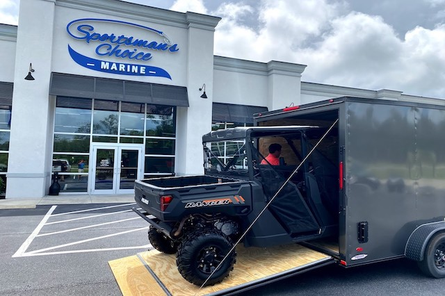 An all black side-by-side recreational vehicle being driven onto an enclosed toy hauler trailer in front of Sportsman's Choice Marine in Longs, SC.